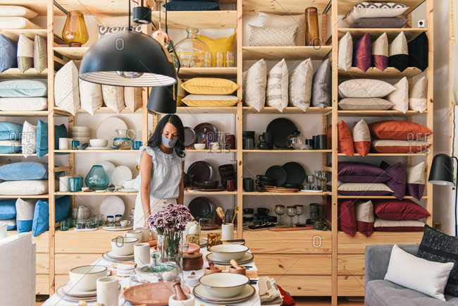 Young woman with mask on shops in boutique home goods store