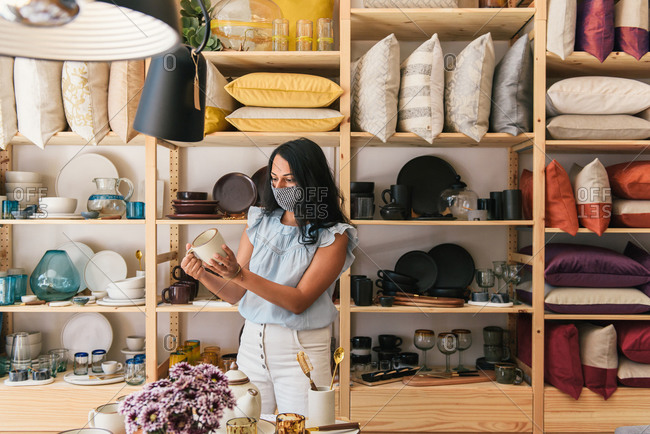 Woman with mask holding up handmade ceramic coffee mug in home store