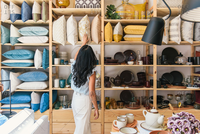 Woman browsing pillows and textiles at boutique home goods store