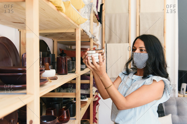 Masked up woman inspecting coasters at luxury home goods store