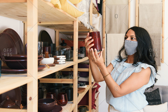 Woman shopping with mask on and looking at glass in boutique store
