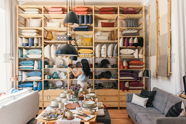 Stylish woman looks through collection of dinnerware at boutique store