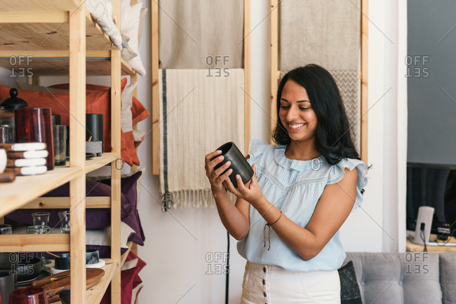 Half body shot of smiling woman holding handmade cup in retail store