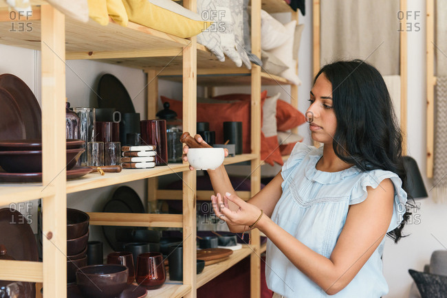 Stylish woman looking at mortar and pestle while shopping home goods