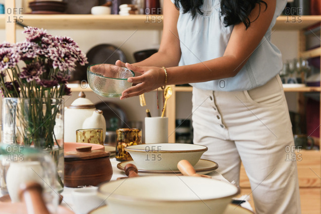 Stylish woman holding glass bowl in boutique home goods store