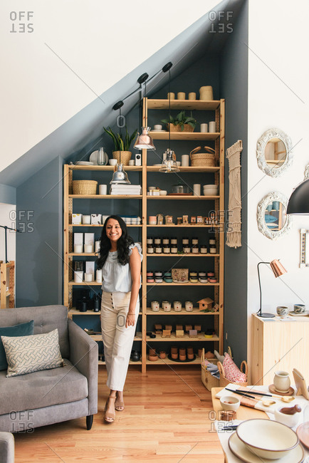 Mid adult woman smiling and posing in front of luxury soaps and candle