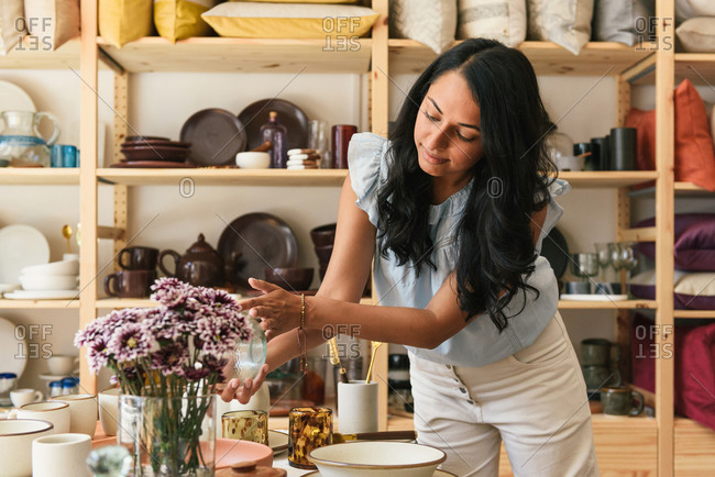 Woman checking the price and detail of artisan home goods in store