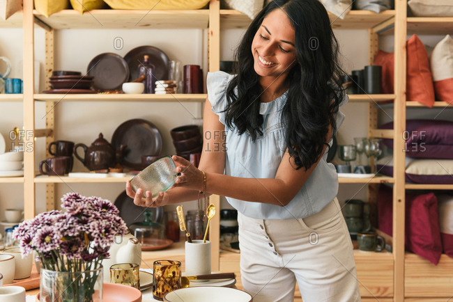 Woman holding and smiling at dinnerware in boutique home decor store