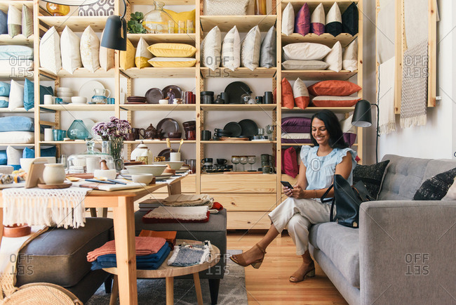 Woman smiling and texting on phone on couch in boutique store