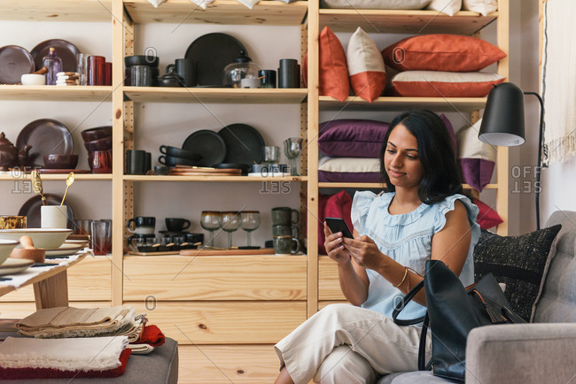 Woman checking messages on phone while waiting for help while shopping