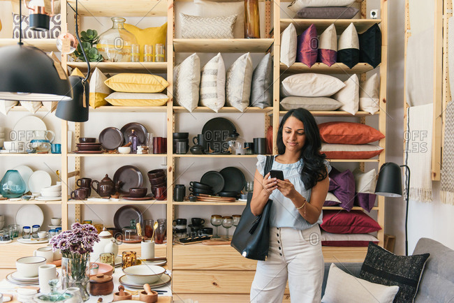 Stylish woman checking messages on phone while shopping in store