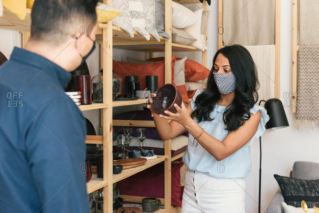 Woman with mask on checking price on product with help from manager