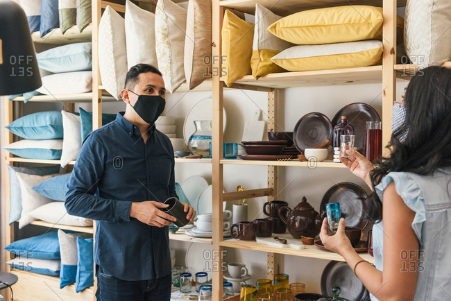 Store manager wearing mask and helping shopper with decor purchase