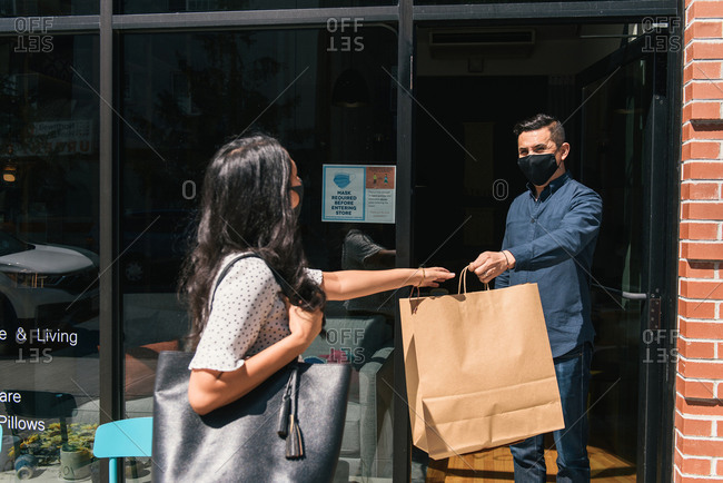 Picking up a purchase at local business while wearing mask