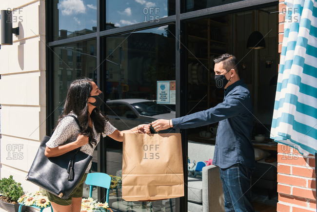 Woman smiling and picking up online purchase curbside from business