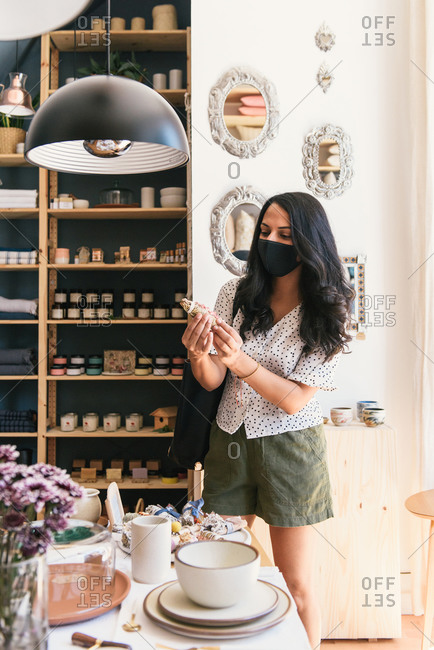 Woman looking over home and beauty products in store with mask on