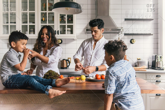 Family lunch time together and mom feeding son sandwich in kitchen