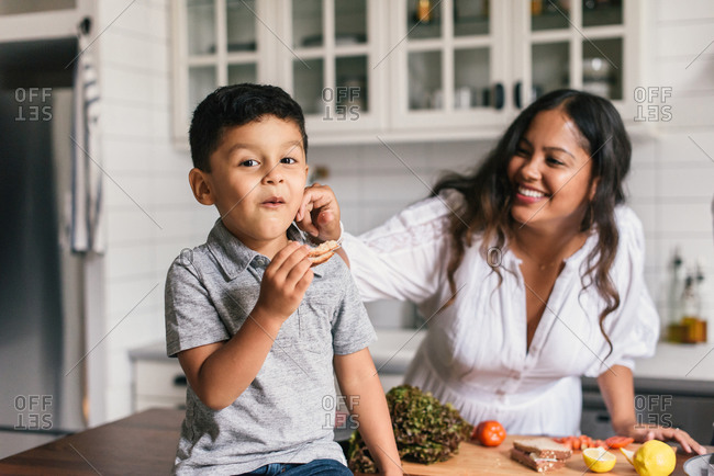 Mother and son having fun together while eating sandwiches in kitchen