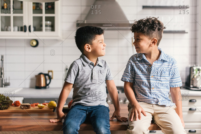 Two boys on stylish kitchen counter making funny faces at each other