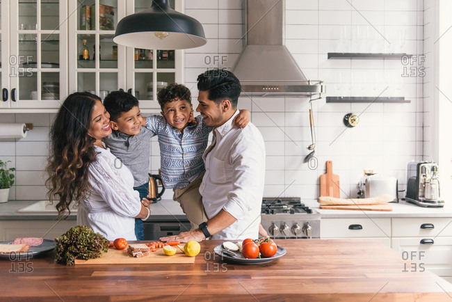 Family hugging and playing with each other in fun kitchen time