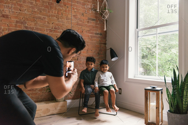 Dad taking phone photos of sons in stylish living room at home