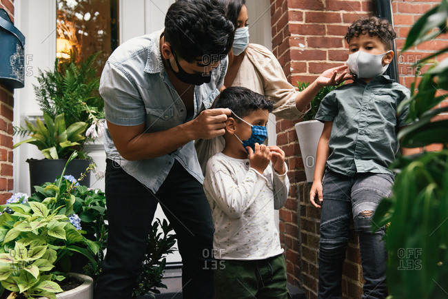 Parents putting masks on children before going out to play from home