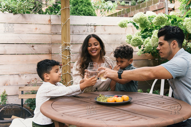 Young family in the backyard cheers with glasses during summer day