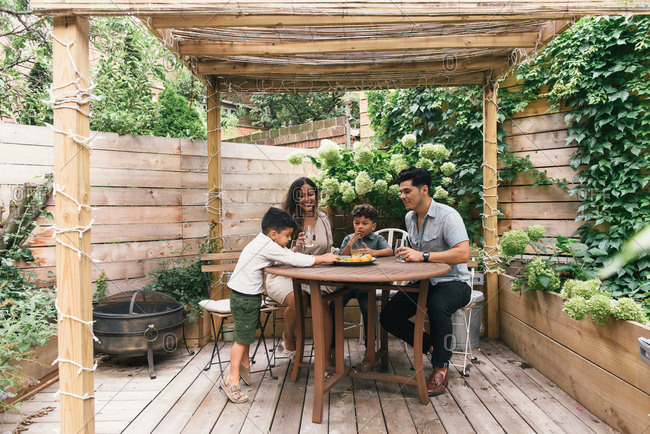 Family together under stylish back yard pergola and table in summer