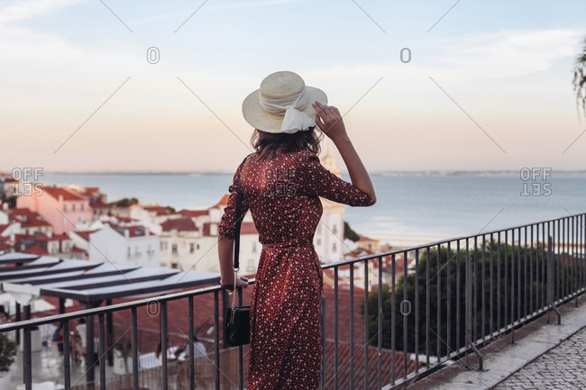 Woman in dress and a straw hat from the back, rooftop Lisbon view