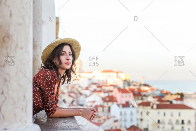 Romantic woman in a straw hat looking over a rooftop view of Lisbon