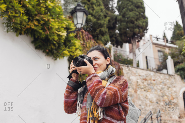 Woman in a sweater taking pictures with a professional camera, Spain