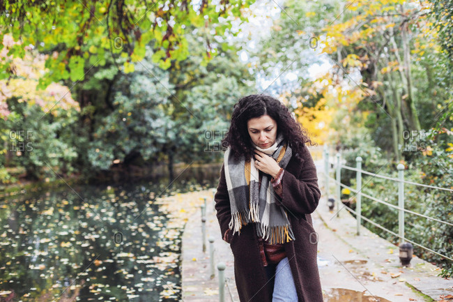 Woman in a coat and scarf looking down, looks sad, walking in a park