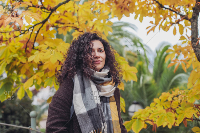 Pretty woman in a scarf with hair on her face, orange leaves, autumn