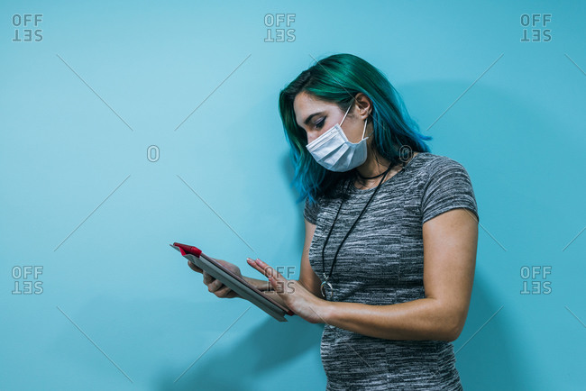 Portrait of a young business woman wearing a mask using a tablet
