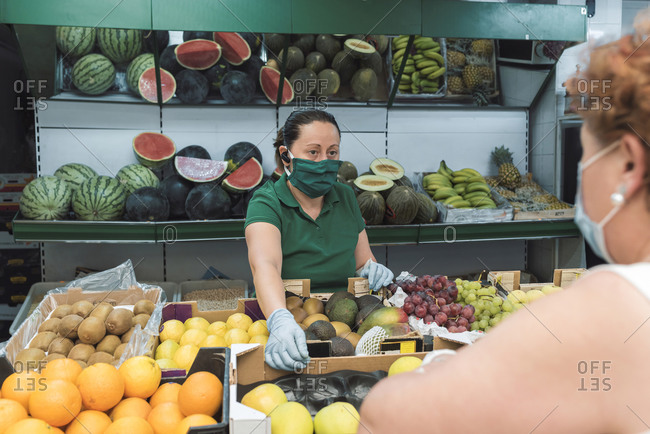 A shopkeeper with a mask attends to a customer in grocery store