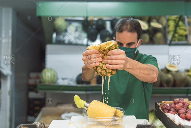 A man squeezing a pineapple in his own fruit shop