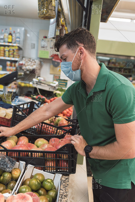 A young man wearing a mask replenishing fruit in the fruit shop