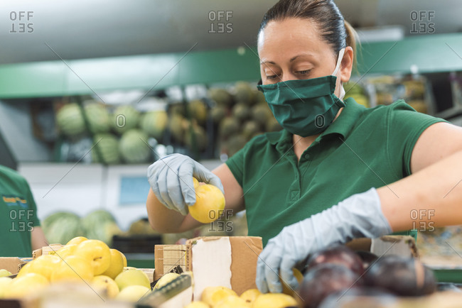 A woman wearing a mask placing fruit in the fruit shop