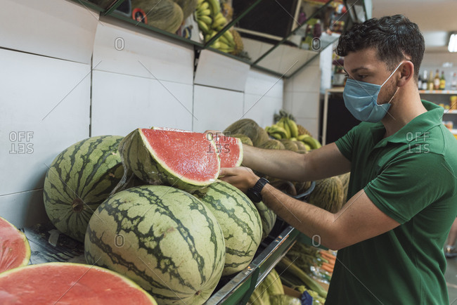 A young man wearing a mask placing watermelons in the fruit shop.