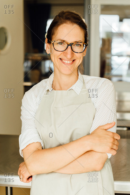 Portrait of female chef in glasses and apron smiling at camera
