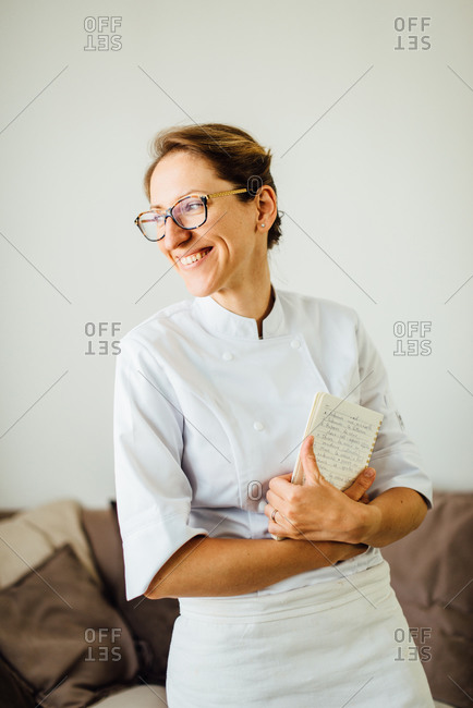 Female chef in uniform holding notebook and smiling