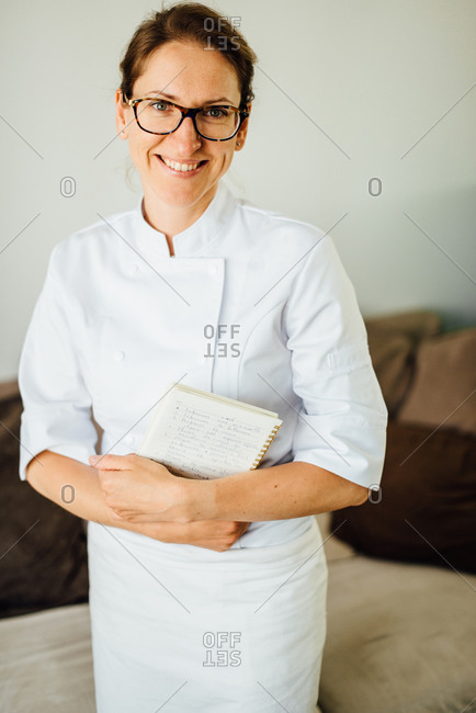 Female chef in uniform holding recipe notebook while smiling at camera