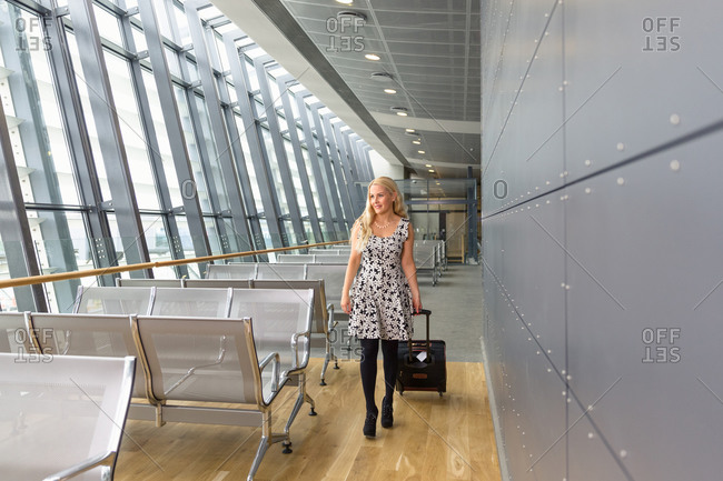 Young woman with suitcase walking in airport hallway