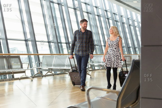 Travelling couple with suitcases walking in airport hallway