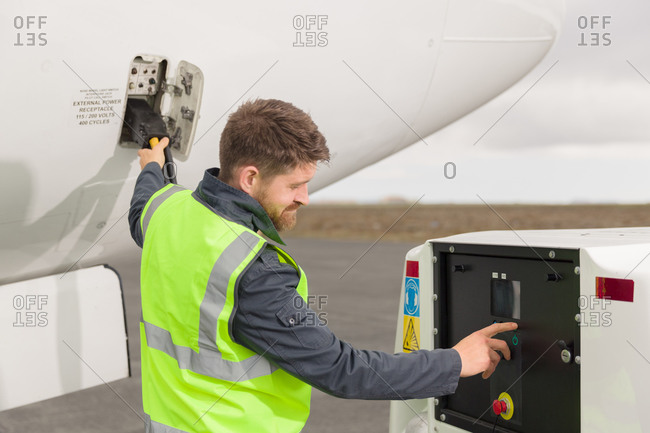 Male technician refueling aircraft on airfield