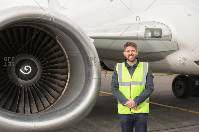 Positive engineer standing near plane