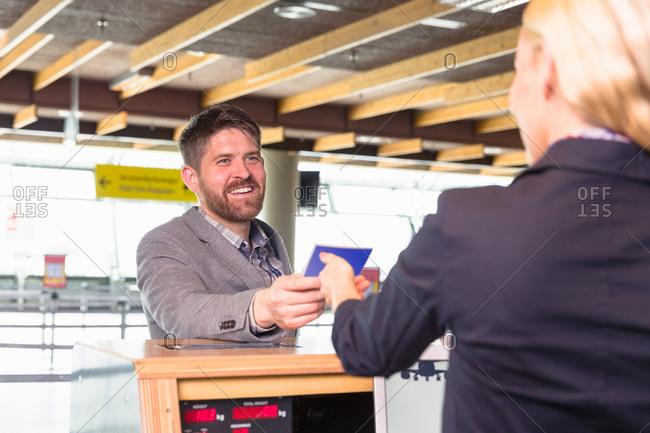 Male traveler giving passport to hostess