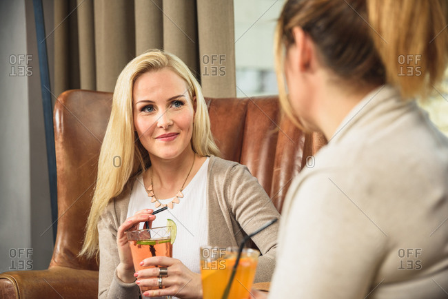 Adult female with cocktail chatting with friend