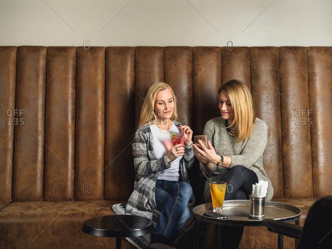 Female friends using smartphone in bar