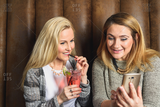 Happy women using smartphone in pub